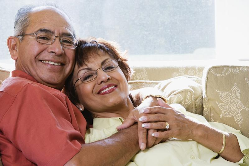 Older couple snuggling on couch | Dentures Gretna LA