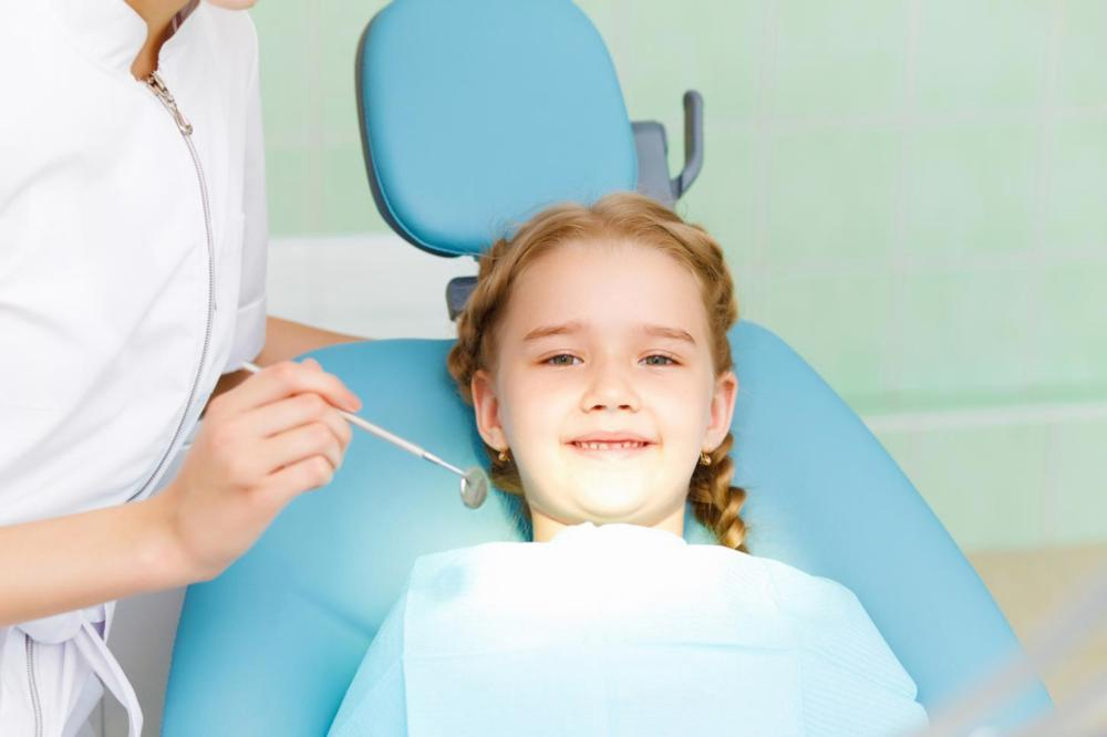 Young girl smiling in dental chair | NOLA Dentures