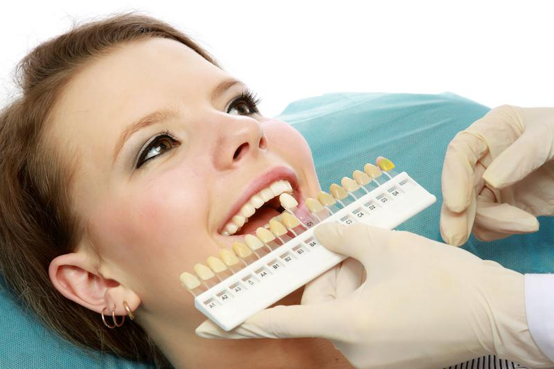 Woman having teeth compared to whitening shades | Teeth Whitening in Gretna, LA