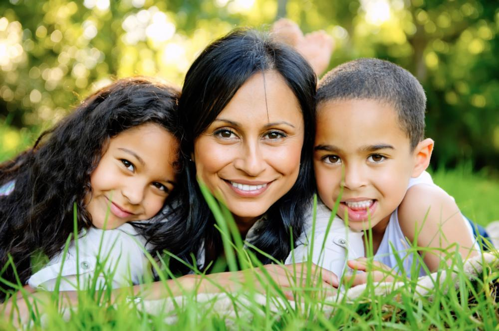 Young boy and girl resting on grass with their Mom | Teeth Whitening Gretna LA
