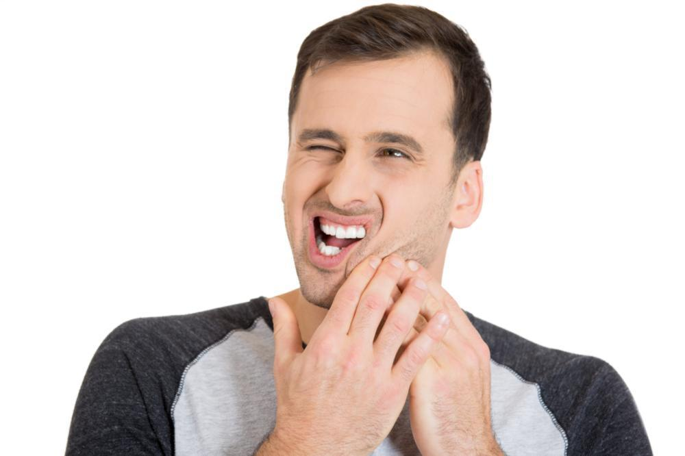 Man holding jaw from tooth pain | Dentist Gretna LA