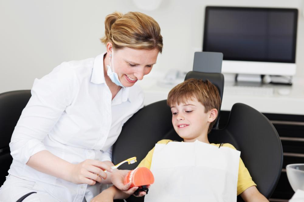 Child sitting in dental chair near dentist | Dentist Gretna LA