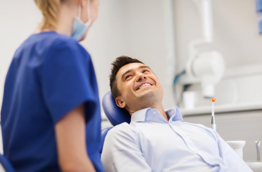 Man Smiling in dental chair as dentist stands next to him | teeth whitening gretna la