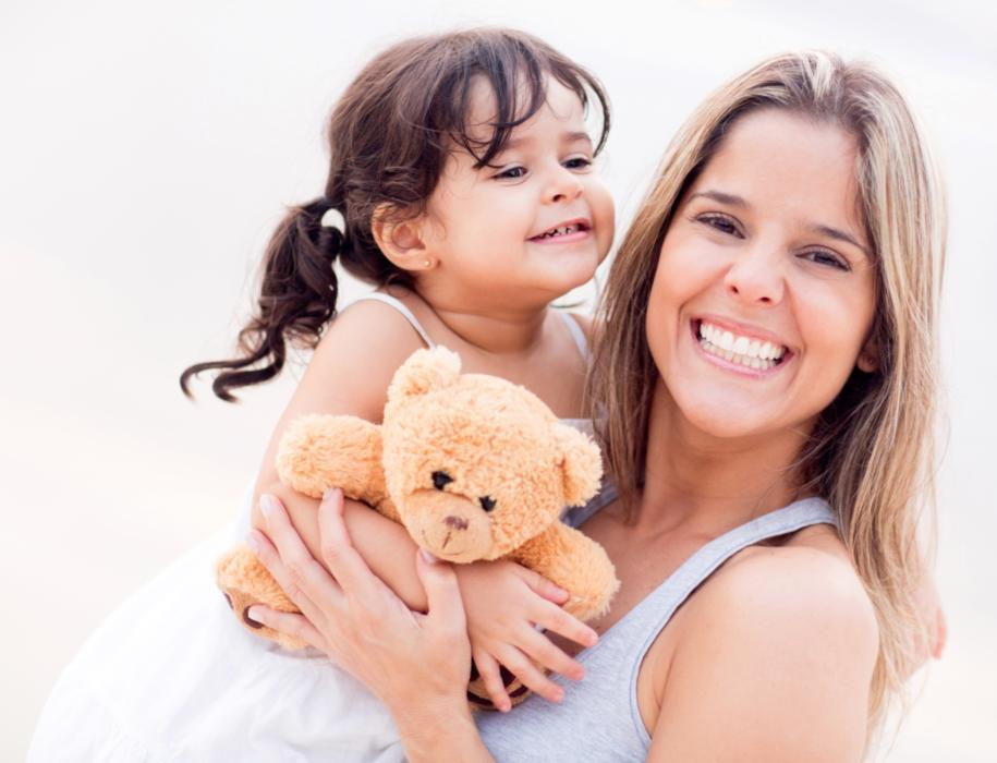 Woman holding daughter with teddy bear | Gretna LA Dentist