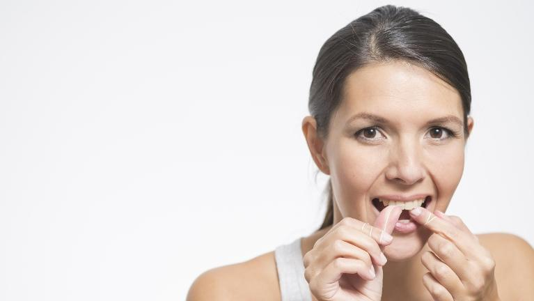 Woman Flossing | Nola Dentures and General Dentistry